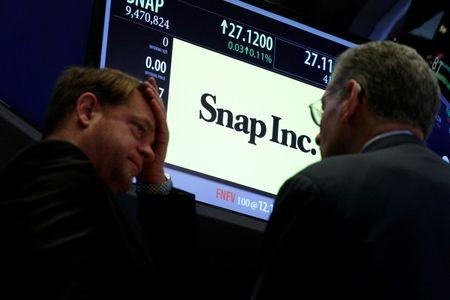 Traders gather at the post where Snap Inc. is traded on the floor of the NYSE