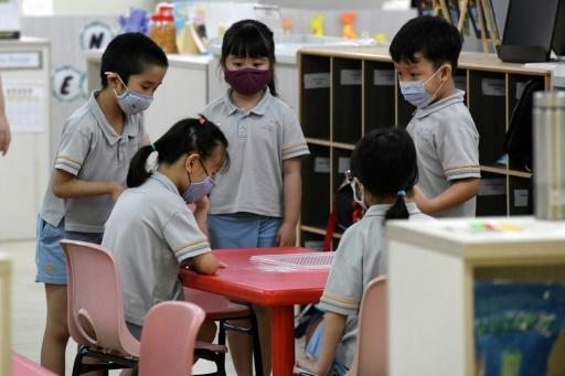 Pupils in masks gather around a table at their school in Singapore