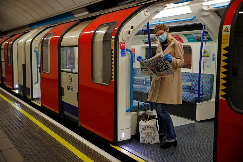 TOPSHOT - A woman wearing PPE (personal protective equipment), including a face mask as a precautionary measure against COVID-19, reads a newspaper as she stands aboard a London Underground Tube train, in the morning rush hour on May 11, 2020, as life in Britain continues during the nationwide lockdown due to the novel coronavirus pandemic. - British Prime Minister Boris Johnson on May 10 announced a phased plan to ease a nationwide coronavirus lockdown, with schools and shops to begin opening from June 1 -- as long as infection rates stay low. (Photo by Tolga Akmen / AFP) (Photo by TOLGA AKMEN/AFP via Getty Images)