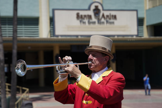 "In this Friday, May 22, 2020 photo, bugler Jay Cohen blows ""Call to the Post"" to the empty grandstand, a tradition maintained for those watching via simulcast, during a day of horse racing at Santa Anita Park in Arcadia, Calif. Horse racing returned to the track after being idled for one and a half months because of public health officials' concerns about the coronavirus pandemic. (AP Photo/Ashley Landis)"