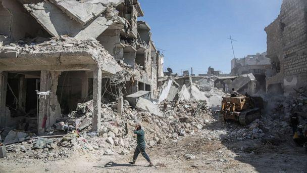PHOTO: A Syrian man reacts as he walks past a building that collapsed following a reported air strike by pro-regime forces. (Anas Alkharboutli/picture alliance via Getty Images)