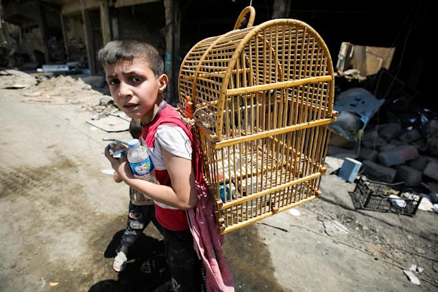 <p>An Iraqi boy carries a birdcage on his back as he flees from the Old City of Mosul on June 20, 2017 during the ongoing offensive by Iraqi forces to retake the last district still held by the Islamic State (IS) group. (Photo: Ahmad al-Rubaye/AFP/Getty Images) </p>