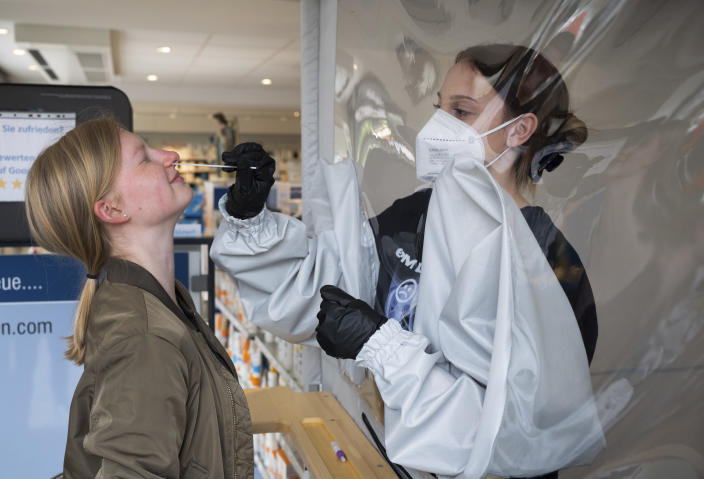 Lea Wittenborg, right, tests her colleague Annika Tschirbs at the Engel pharmacy in Soest, Germany, Wednesday, May 12, 2021. Germany's coronavirus infection rate dropped to its lowest level in nearly two months on Friday, while the health minister said the country had the most successful day yet of its vaccination campaign this week. (Bernd Thissen/dpa via AP)