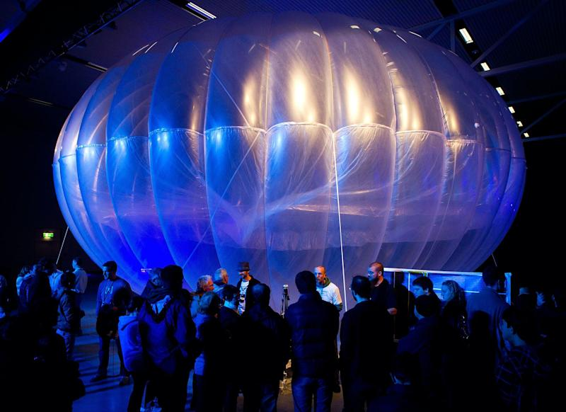 Visitors stand next to a high altitude WiFi internet hub, a Google Project Loon balloon, on display at the Airforce Museum in Christchurch on June 16, 2013: AFP PHOTO / MARTY MELVILLE