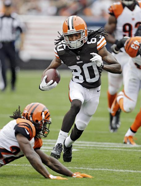 Cleveland Browns wide receiver Travis Benjamin (80) avoids Cincinnati Bengals cornerback Adam Jones on a 39-yard pass reception in the first quarter of an NFL football game on Sunday, Sept. 29, 2013, in Cleveland. (AP Photo/Tony Dejak)