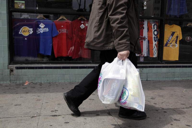 A man walks along the street with plastic bags in Los Angeles, Thursday, May 24, 2012. Now that the city of Los Angeles has taken the first step toward banning plastic bags, it appears the little utilitarian bags themselves may be headed for the trash heap of history. (AP Photo/Jae C. Hong)
