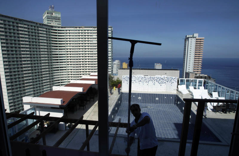 In this Feb. 7, 2014 photo, Raidel Utria cleans glass doors at La Florentina restaurant where the empty rooftop pool can be seen behind at the Capri hotel in Havana, Cuba. After apparently sitting idle for years, restoration began about four years ago according to hotel officials. Workers are still refurbishing some rooms and laying carpeting on some floors. Finishing touches are being put on the rooftop pool, which boasts stunning views of the Florida Straits. (AP Photo/Franklin Reyes)