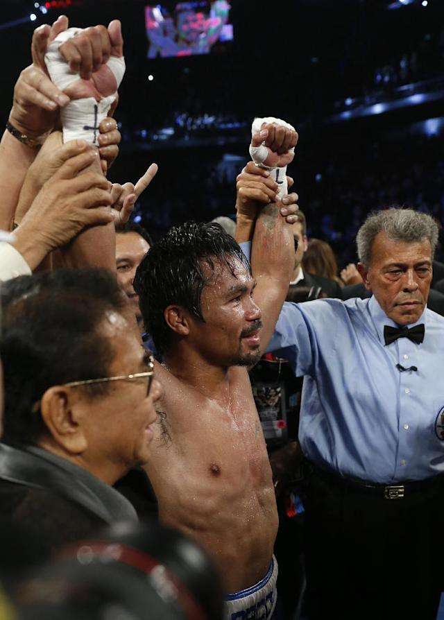 WBO welterweight champion Manny Pacquiao celebrates after defeating WBO junior welterweight champion Chris Algieri of the United States during their world welterweight title boxing match at the Venetian Macao in Macau, Sunday, Nov. 23, 2014. (AP Photo/Kin Cheung)