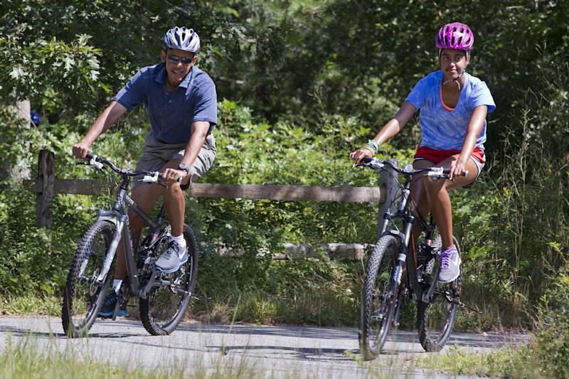 President Barack Obama and daughter Malia ride their bikes in Manuel F. Correllus State Forest in West Tisbury, Mass., after first lady Michelle Obama, with daughter Sasha, passed by first, Friday, Aug. 16, 2013, during their family vacation on the island of Martha's Vineyard. (AP Photo/Jacquelyn Martin)