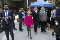 Environmental activist Greta Thunberg, center, of Sweden, walks with an entourage after passing a security checkpoint while appearing at the United Nations, Monday, Sept. 23, 2019 in New York. (AP Photo/Mark Lennihan)
