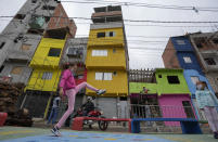 Workers paint the facades of residences in the Paraisopolis favela, as a child plays in the foreground during the community's centennial celebration, in Sao Paulo, Brazil, Thursday, Sept. 16, 2021. One of the largest favela's in Brazil, home to tens of thousands of residents in the country's largest and wealthiest city, Paraisopolis is grappling with crime and a pandemic that have challenged daily life for many who live there, but organizers say its people have built a vibrant community and are launching a 10-day celebration of its achievements. (AP Photo/Andre Penner)