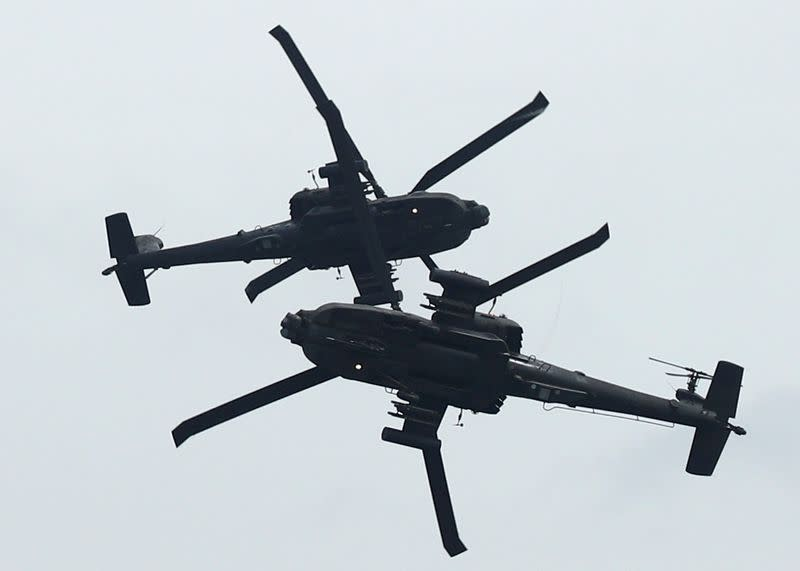 Singapore's Republic of Singapore Air Force (RSAF) AH64 Apache Longbow aircrafts perform an aerial display during a media preview of the Singapore Airshow in Singapore