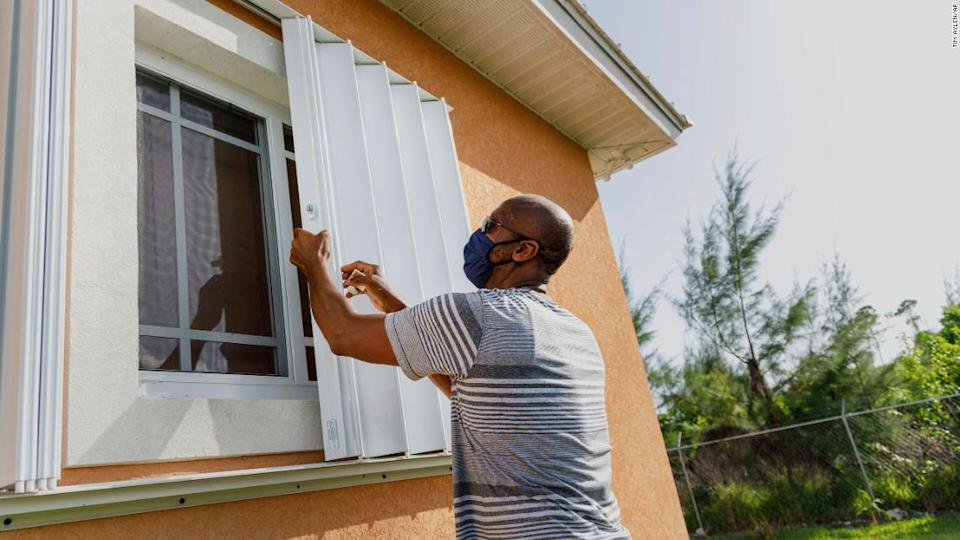 """<p>Wendell Smith unfolds storm shutters at his home in Freeport in the Bahamas on Friday, July 31, 2020. </p><div class=""""cnn--image__credit""""><em><small>Credit: Tim Aylen/AP / Associated Press</small></em></div>"""