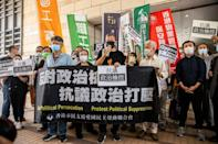 Pro-democracy activist Lee Cheuk-yan (C) speaks to the media next to former lawmaker Cyd Ho (centre L) outside West Kowloon Court in Hong Kong on April 1, 2021