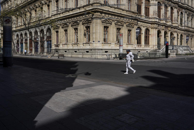 A woman walks through an empty street during a nationwide confinement to prevent the spread of the coronavirus, in the center of Lyon, central France, Sunday, April 5, 2020. The new coronavirus causes mild or moderate symptoms for most people, but for some, especially older adults and people with existing health problems, it can cause more severe illness or death. (AP Photo/Laurent Cipriani)