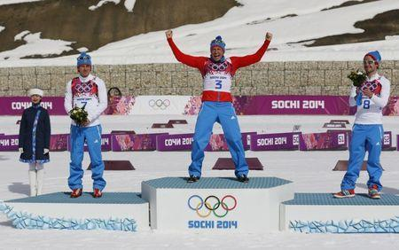 Russia's Maxim Vylegzhanin, Alexander Legkov and Ilia Chernousov (L-R) celebrate during the flower ceremony for the men's cross-country 50 km mass start free event at the Sochi 2014 Winter Olympic Games February 23, 2014. REUTERS/Stefan Wermuth