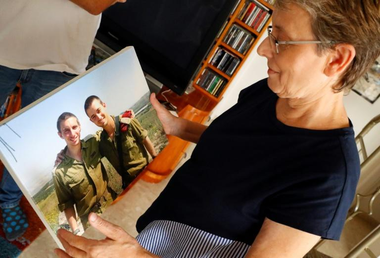 Lean Goldin holds a picture of her son Hadar (L) in the family home in Kfar Saba, central Israel (AFP Photo/JACK GUEZ)