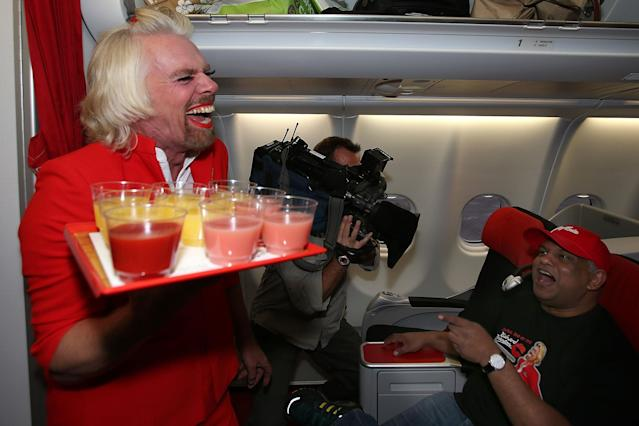 PERTH, AUSTRALIA - MAY 12: Sir Richard Branson serves drinks to Tony Fernandes prior to their flight to Kuala Lumpur at Perth International Airport on May 12, 2013 in Perth, Australia. Sir Richard Branson lost a friendly bet to AirAsia Group Chief Executive Officer Tony Fernandez after wagering on which of their Formula One racing teams would finish ahead of each other in their debut season of the 2010 Formula One Grand Prix in Abu Dhabi and that the loser would serve as a female flight attendant on board the winner's airline. (Photo by Paul Kane/Getty Images)