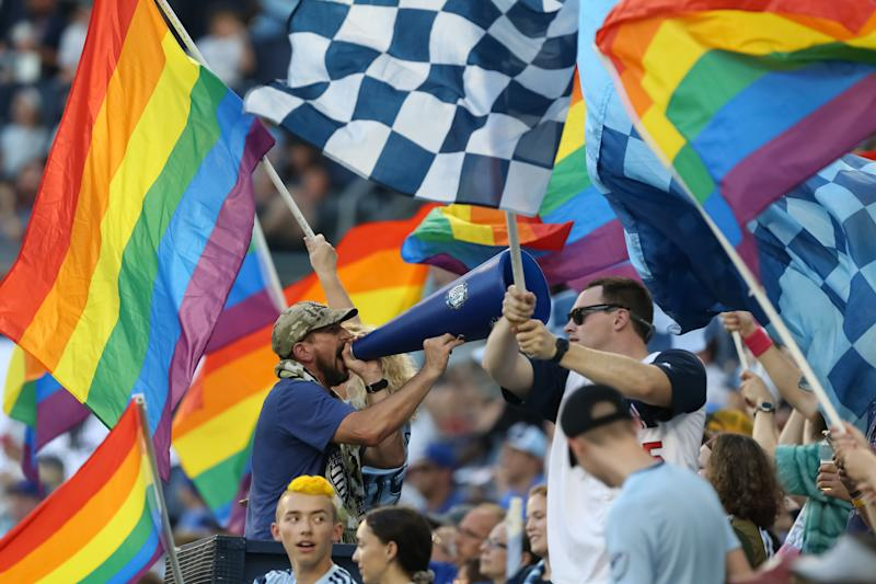 KANSAS CITY, KS - AUGUST 17: A Sporting Kansas City fan yells in a megaphone while flags fly around him during an MLS match between the San Jose Earthquakes and Sporting Kansas City on August 17, 2019 at Children's Mercy Park in Kansas City, KS. (Photo by Scott Winters/Icon Sportswire via Getty Images)