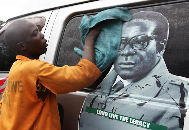 <p>Youth washes a minibus adorned with picture of President Robert Mugabe at a bus terminus in Harare, Zimbabwe, Nov. 15, 2017. (Photo: Philimon Bulawayo/Reuters) </p>