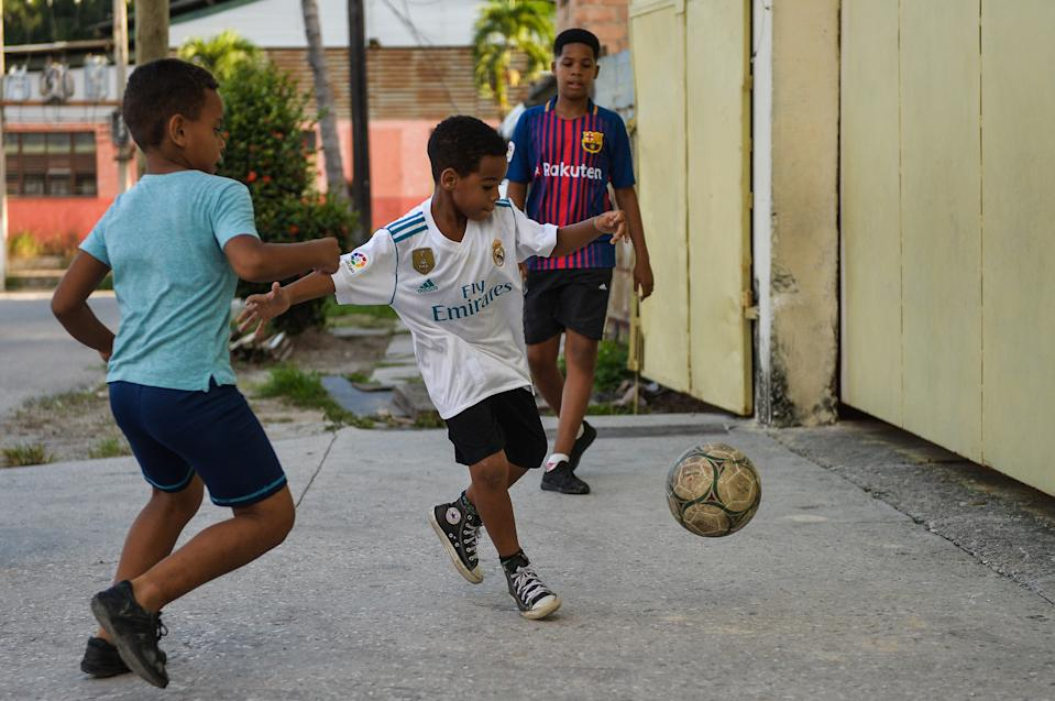 Cuban children wearing their favourite football team uniforms play football, in Havana, on October 19, 2018. - Football took over baseball in the preference of children and young people in Cuba, where the latter has been king for almost 150 years. (Photo by Yamil LAGE / AFP)        (Photo credit should read YAMIL LAGE/AFP via Getty Images)