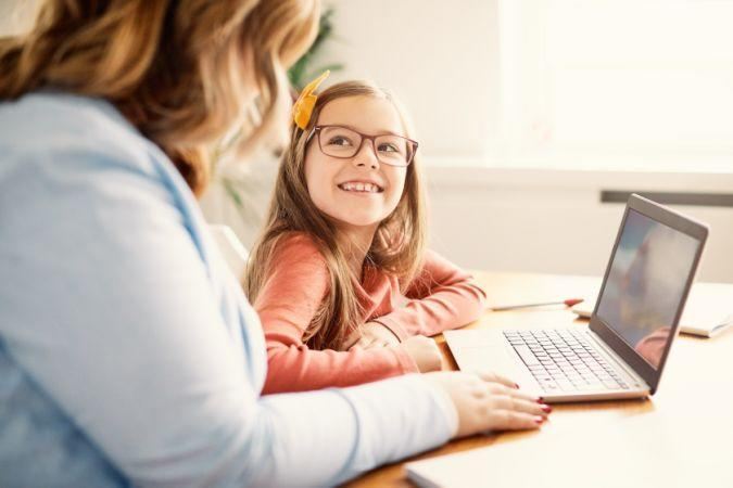 Mother and daughter Having fun with laptop at home