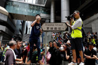 FILE - In this June 21, 2019, file photo, pro-democracy activist Joshua Wong, center left, speaks as protesters surround the police headquarters in Hong Kong. Demosisto, a pro-democracy group in Hong Kong, posted on its social media accounts that well-known activist Wong had been pushed into a private car around 7:30 a.m. Friday, Aug. 30, 2019 and was taken to police headquarters. It later said another member, Agnes Chow, had also been arrested, at her home. (AP Photo/Vincent Yu, File)