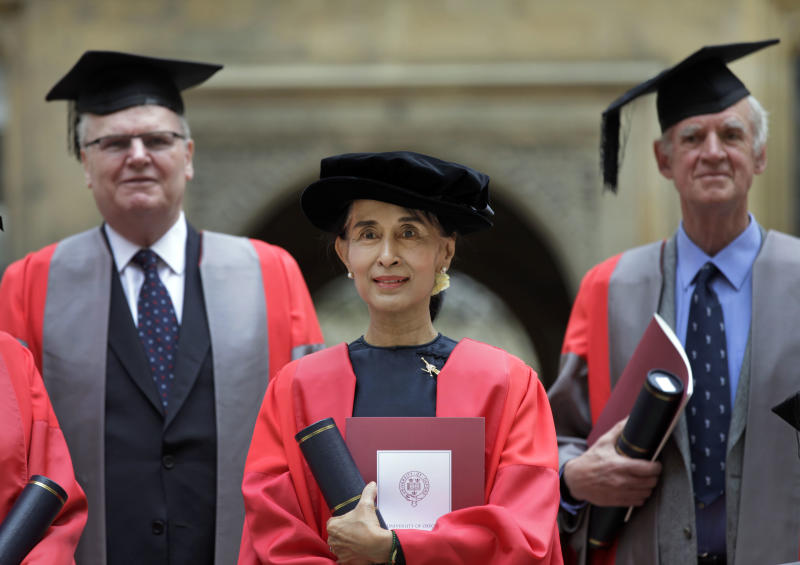 """Myanmar opposition leader Aung San Suu Kyi, poses for the photographers following an award ceremony at the Oxford University, Oxford, England, on Wednesday, June 20, 2012. It was a long wait, but Aung San Suu Kyi has finally received her honorary degree from Oxford University. In her speech, Suu Kyi praised the role Oxford played in helping her see humankind at its best during her long years under house arrest in Myanmar. """"The most important thing that I learned was respect for all of civilization,"""" she said, wearing a traditional red gown. """"In Oxford I learned to respect all that is best in human civilization. That helped me cope with something that was not quite the best."""" (AP Photo/Lefteris Pitarakis)"""