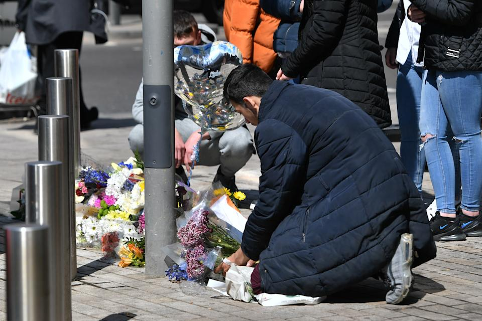 People place flowers at the scene in Barking Road, East Ham, where 14-year-old Fares Maatou was knifed to death on Friday. Picture date: Saturday April 24, 2020.