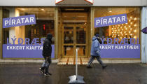 People walk past the Pirate Party election office in Reykjavik, Iceland, Wednesday, Sept. 22, 2021. Climate change is top of the agenda when voters in Iceland head to the polls for general elections on Saturday, following an exceptionally warm summer and an election campaign defined by a wide-reaching debate on global warming. The Pirate Party wants to support a plant-based diet among the population. (AP Photo/Brynjar Gunnarsson)