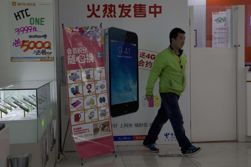 """A man walks in front of a China Telecom advertisement for the iPhone with the Chinese characters """"Hot Sales"""" in Beijing Monday, Dec. 16, 2013. Apple Inc. might have a chance to pep up cooling iPhone sales in China if it finally can reach a deal with the world's biggest phone carrier. (AP Photo/Ng Han Guan)"""