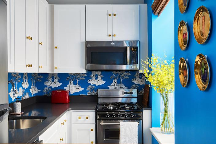 Brass hardware and white cabinetry are paired with a bright blue wallpaper. The white space allows the printed backsplash to shine.