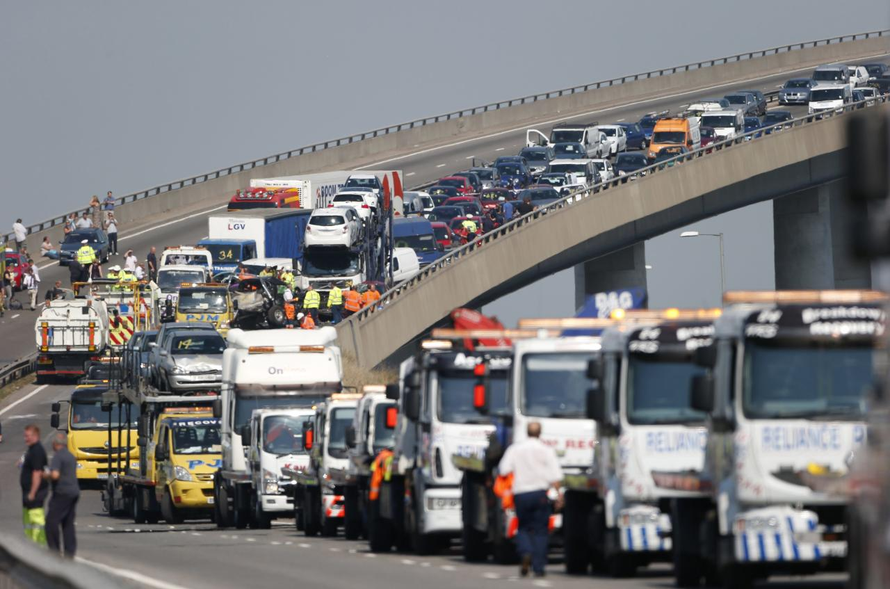 Recovery trucks line up to collect over 100 vehicles involved in multiple collisions, which took place in dense fog during the morning rush hour, on the Sheppey Bridge in Kent, east of London, September 5, 2013. Eight people were seriously injured and dozens hurt in the multiple crashes. REUTERS/Suzanne Plunkett (BRITAIN - Tags: TRANSPORT DISASTER)