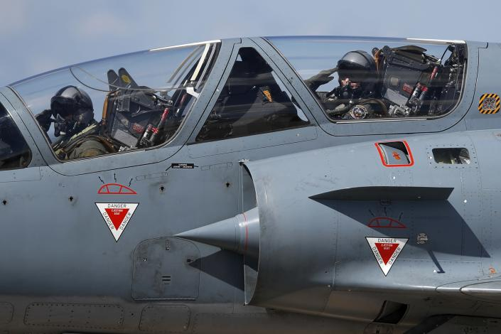 Greek crew of a Mirage 2000-5 salute as they taxi at Andravida air base, about 279 kilometres (174 miles) southwest of Athens, Tuesday, April 20, 2021. Greece vowed Tuesday to expand military cooperation with traditional NATO allies as well as Middle Eastern powers in a race to modernize its armed forces and face its militarily assertive neighbor Turkey. (AP Photo/Thanassis Stavrakis)