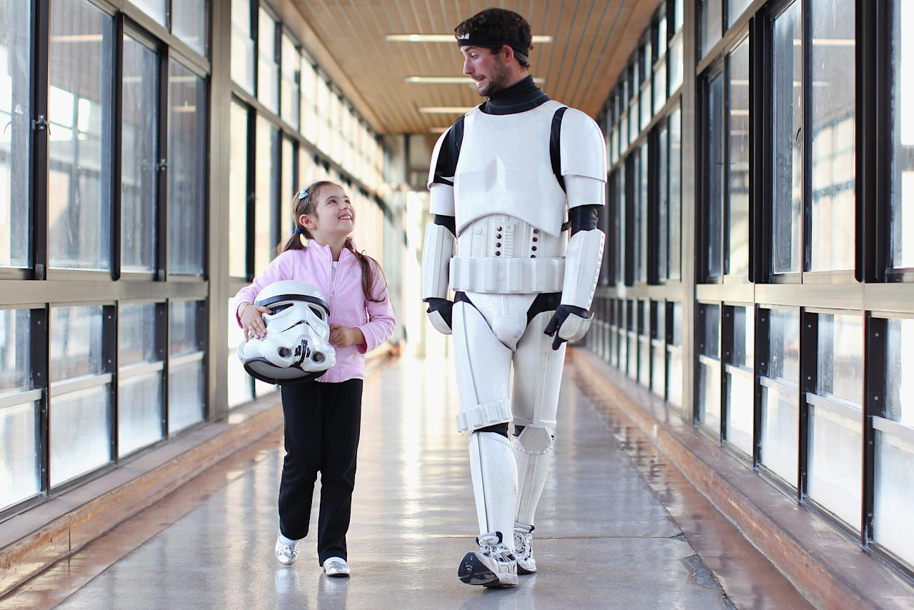 Jacob French walks with patient Helena Kantarelis at the Sydney Children's Hostpital on April 4, 2012 in Sydney, Australia. French today completed the over 5,000 km trek from Perth to Sydney on foot, donning a full body stormtrooper costume he successfully raised over $100,000 for the Starlight Children's Foundation. Since July 2011, Jacob has walked 10 hours a day, Monday to Friday, lost over 12kg in weight, and gone through seven pairs of shoes. The Starlight Children's Foundation provides programs to help lift the spirits of sick children in hospitals accross Australia.  (Photo by Cameron Spencer/Getty Images)