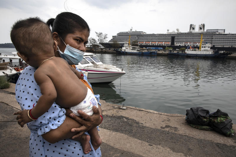 SIHANOUKVILLE - FEBRUARY 17 : A Cambodian woman wears a mask holding her baby on the dock outside the MS Westerdam cruise ship docked in Sihanoukville, Cambodia on February 17, 2020. There are currently 233 passengers and 747 crew members on board who were tested again. As the ship was declared free of the Coronavirus (COVID-19 ) over 1,000 passengers took charter flights to Phnom Penh, one elderly American woman was later found to be infected while transiting in Malaysia. The cruise ship departed Hong Kong February 1st with 1,455 passengers and 802 crew on board. (Photo by Paula Bronstein/Getty Images )