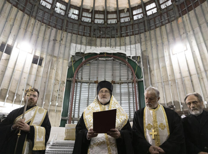 In this Dec. 6, 2019 photo, Greek Orthodox Archbishop Elpidophoros, center, leads clergy in a celebration of St. Nicholas Day inside the St. Nicholas National Shrine at the World Trade Center in New York. Two years after a lack of funds halted construction of the marble-clad Greek Orthodox church, Gov. Andrew Cuomo and Greek Orthodox officials announced plans Thursday, Jan. 2, 2020, to resume construction with the goal of finishing the rebuilding by the 20th anniversary of the terrorist attacks of Sept. 11, 2001. (AP Photo/Mark Lennihan)