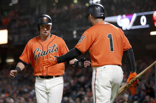San Francisco Giants' Joe Panik, left, is congratulated by teammate Gregor Blanco (1) after scoring a run on a Austin Slater single against the Colorado Rockies during the second inning of a baseball game in San Francisco, Friday, Sept. 14, 2018. (AP Photo/Tony Avelar)