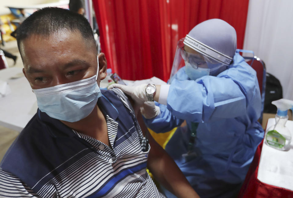 A man receive shots of the AstraZeneca vaccine during a vaccination campaign in Bekasi on the outskirts of Jakarta, Indonesia, Thursday, June 17, 2021. (AP Photo/Achmad Ibrahim)