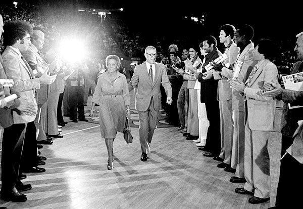 """John and Nell Wooden pass between former UCLA players who are honoring Wooden on his 65th birthday on Oct. 14, 1975, at Pauley Pavilion. <span class=""""copyright"""">(Associated Press)</span>"""