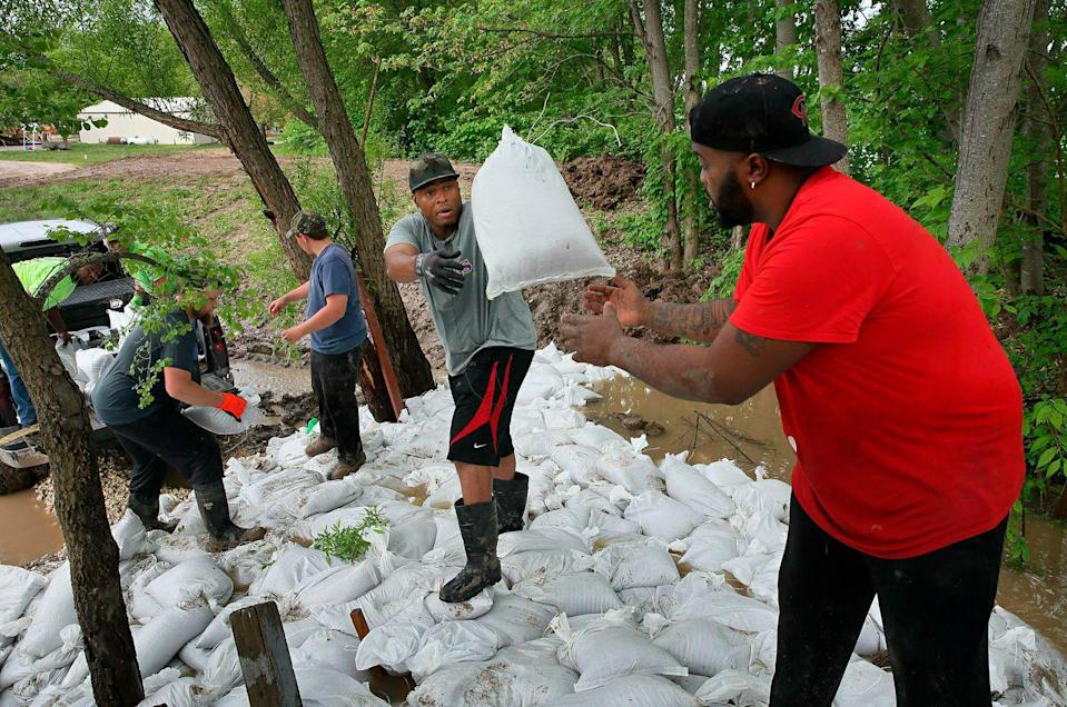 <p>Marcus Gilbert, center, tosses a sandbag to Herman Drones as they and other volunteers work to plug the leaks in a levee at Cherokee Lakes Campground in O'Fallon, Mo.</p>