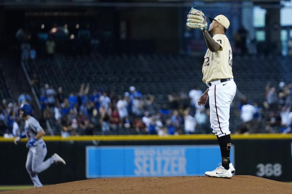 Arizona Diamondbacks starting pitcher Humberto Mejia, right, gets a new baseball after giving up a home run to Los Angeles Dodgers' Trea Turner, left, during the first inning of a baseball game Sunday, Sept. 26, 2021, in Phoenix. (AP Photo/Ross D. Franklin)