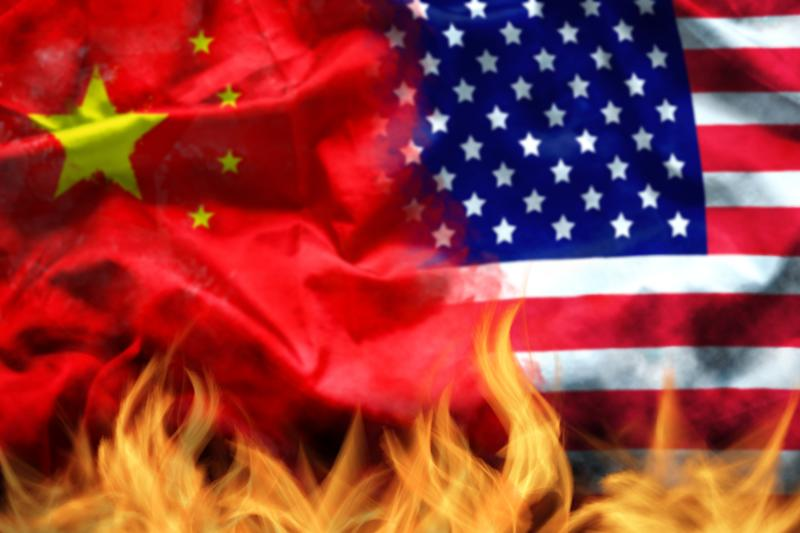 waving USA and China flag with fire on foreground. serious trade tension or trade war between US and China, financial concept