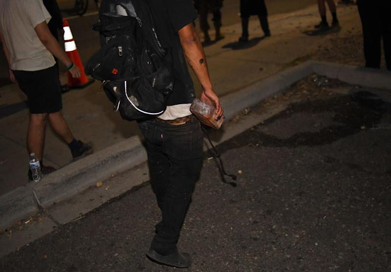 A man hold a brick in his hand during a protest in Denver. Source: Getty
