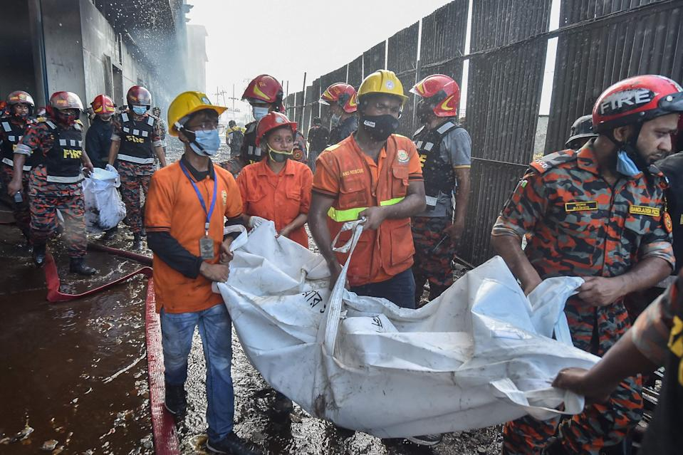 Firefighters and rescue workers recover bodies of the deceased who died in the fire (AFP via Getty Images)