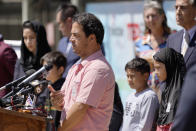 """FILE - In this Thursday, Sept. 2, 2021 file photo, Mohammad Faizi, center, speaks during a news conference in El Cajon, Calif. He and his family were visiting relatives in Afghanistan in August, and were forced to escape as the Taliban seized power. Faizi, a green card holder from the San Diego suburb of El Cajon, said he and his wife and five children were stopped by the Taliban at a checkpoint on their way to the airport. His wife is a U.S. citizen. Faizi, whose family got out just before the last U.S. flight left, said he was asked at the checkpoint why he was trying to leave Afghanistan. """"I told him, that's our country. That's my nation. We're living there. So we have to get out of here."""" (AP Photo/Gregory Bull)"""