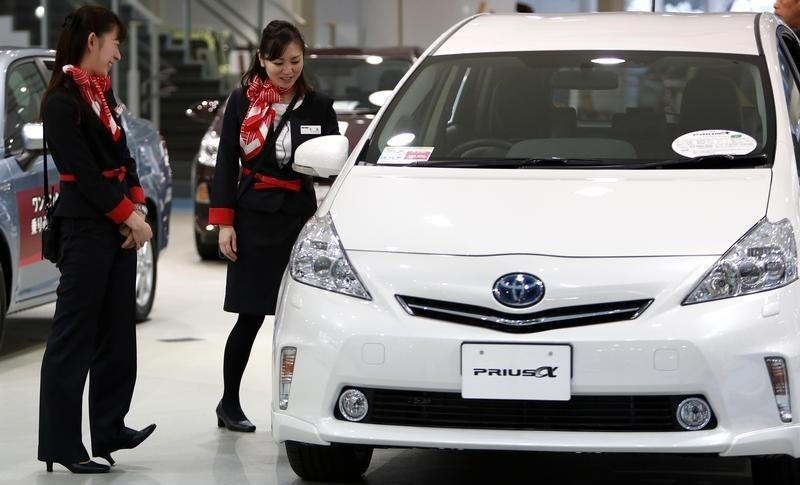 Showroom staff chat next to a Toyota Motor Corp Prius Alpha at its showroom in Tokyo