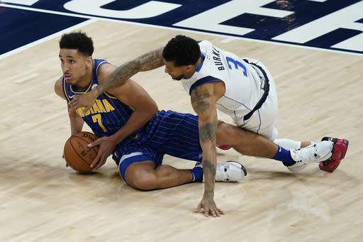 Indiana Pacers' Malcolm Brogdon (7) and Dallas Mavericks' Trey Burke (3) battle for a loose ball during the second half of an NBA basketball game, Wednesday, Jan. 20, 2021, in Indianapolis. (AP Photo/Darron Cummings)