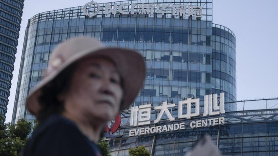 A woman walks past the Evergrande Center in Shanghai, China, 21 September 2021.