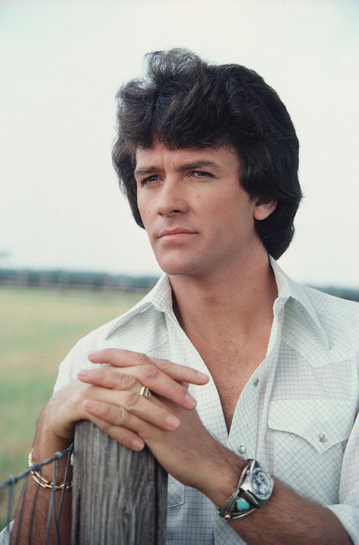 A promotional still from the American television series 'Dallas' shows Patrick Duffy (as Bobby Ewing) as he leans on a fencepost, July 1979. (Photo by CBS Photo Archive/Getty Images)